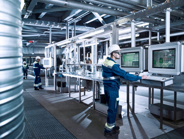 Plusieurs ouvriers qui manipulent des ordinateurs et bases de données dans un entrepôt industriel
