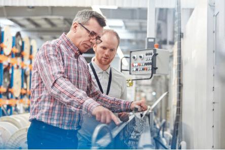 deux hommes devant une machine industrielle